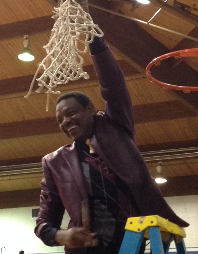 Huston-Tillotson head coach Maurice Callis cuts the net following the Lady Rams' first RRAC tournament championship.